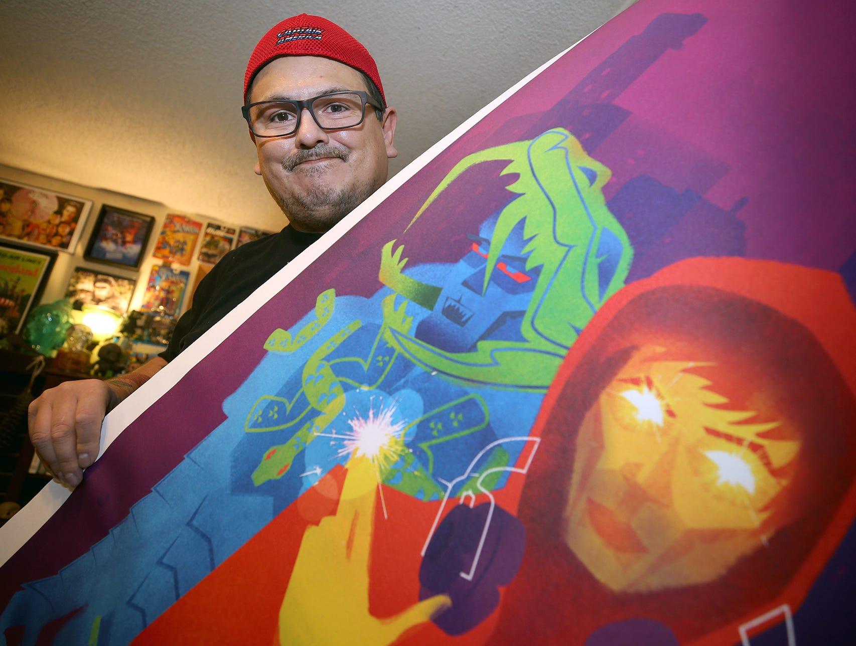S'Klallam artist Jeffrey Veregge has an exhibit in the Smithsonian National Museum of the American Indian in New York City that will show off some of his work illustrating Marvel superheroes over the next year. He is holding a poster print, used to show the colors for the Smithsonian Museum.