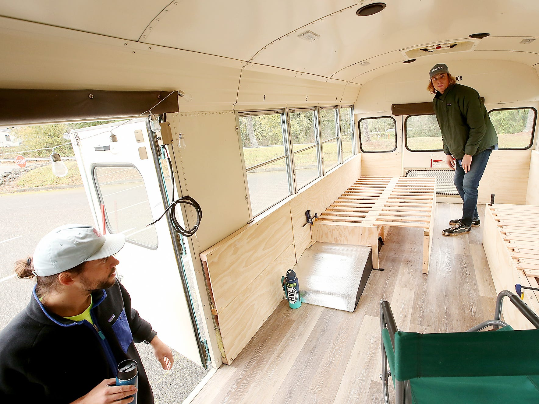 Hans Schippers extends a custom bed frame that he and Nick (at left) are building and installing during a tour of the bus they are renovating to travel down the coast in while teaching students about the ways they can reduce their use of plastics and live more sustainable lives. In partnership with Sustainable Coastlines Hawaii, the brothers hope to reach 10,000 students during the trip.