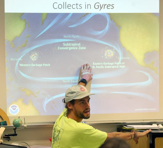 Nick Schippers talks to students about the various gyres that move and trap plastic in certain places in the Pacific Ocean while he and his brother Hans give a presentation to a science class at Kingston Middle School on Thursday, November 15, 2018.