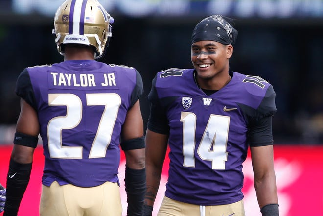 Huskies defensive back JoJo McIntosh (14) talks with teammate Keith Taylor during a September game against North Dakota.