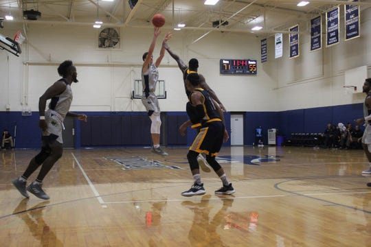 Austin Butler shoots a three-pointer over a Point University defender on Nov. 14.