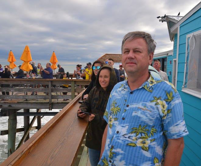 Alexandor Sarvkin and Ekaterina Timofeeva from Russia try to get a glimpse of the rocket through the clouds. Low clouds gave viewers at the Cocoa Beach Pier just a few seconds of visibility too see the launch of the SpaceX Falcon 9 rocket from Kennedy Space Center's Pad 39A. The rocket, launched at 3:46 Thursday afternoon, carried at Es'hail-2 communications satellite.