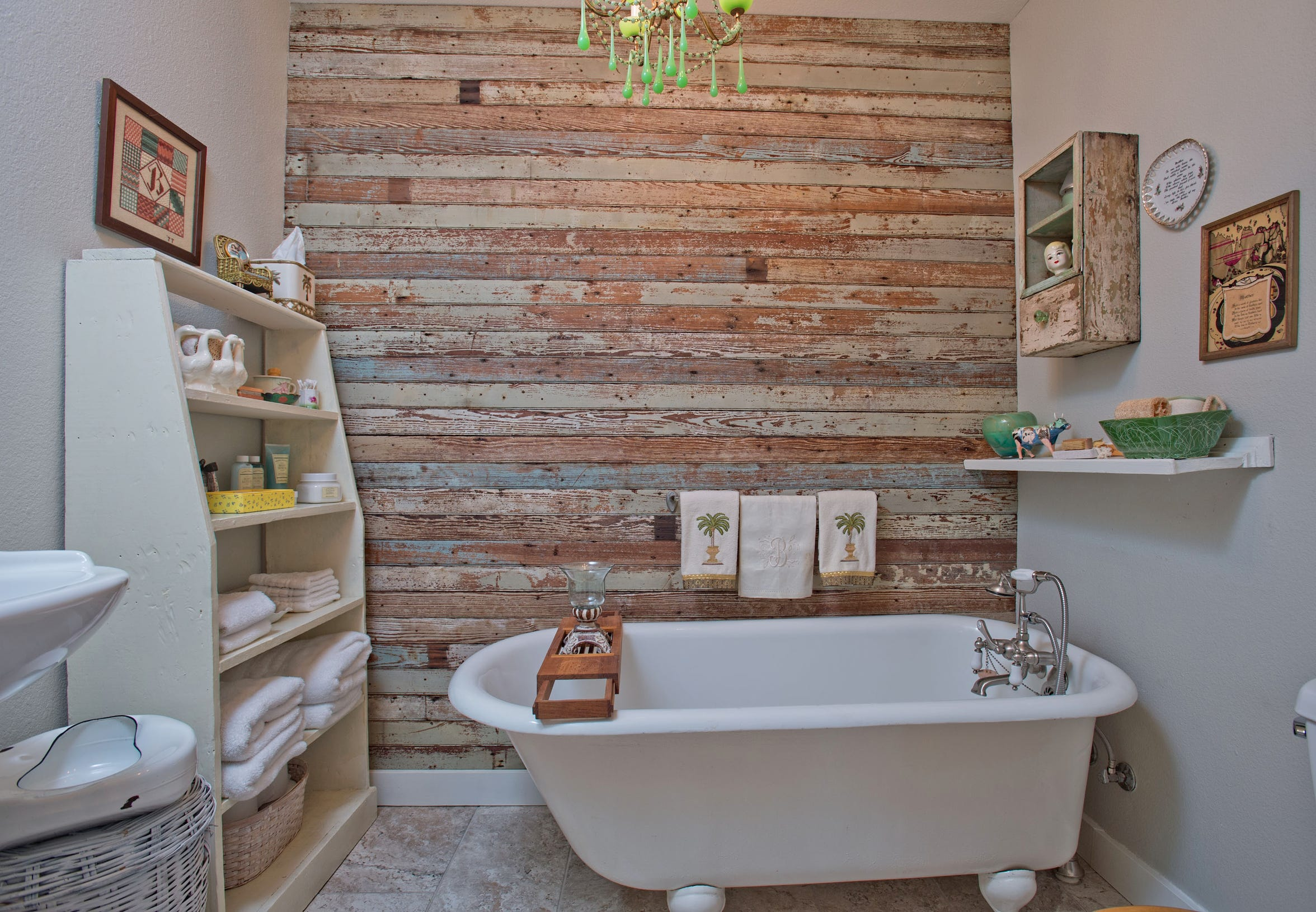 An antique tub sits among a reclaimed wood wall setting a perfect vintage vibe in the guest bath