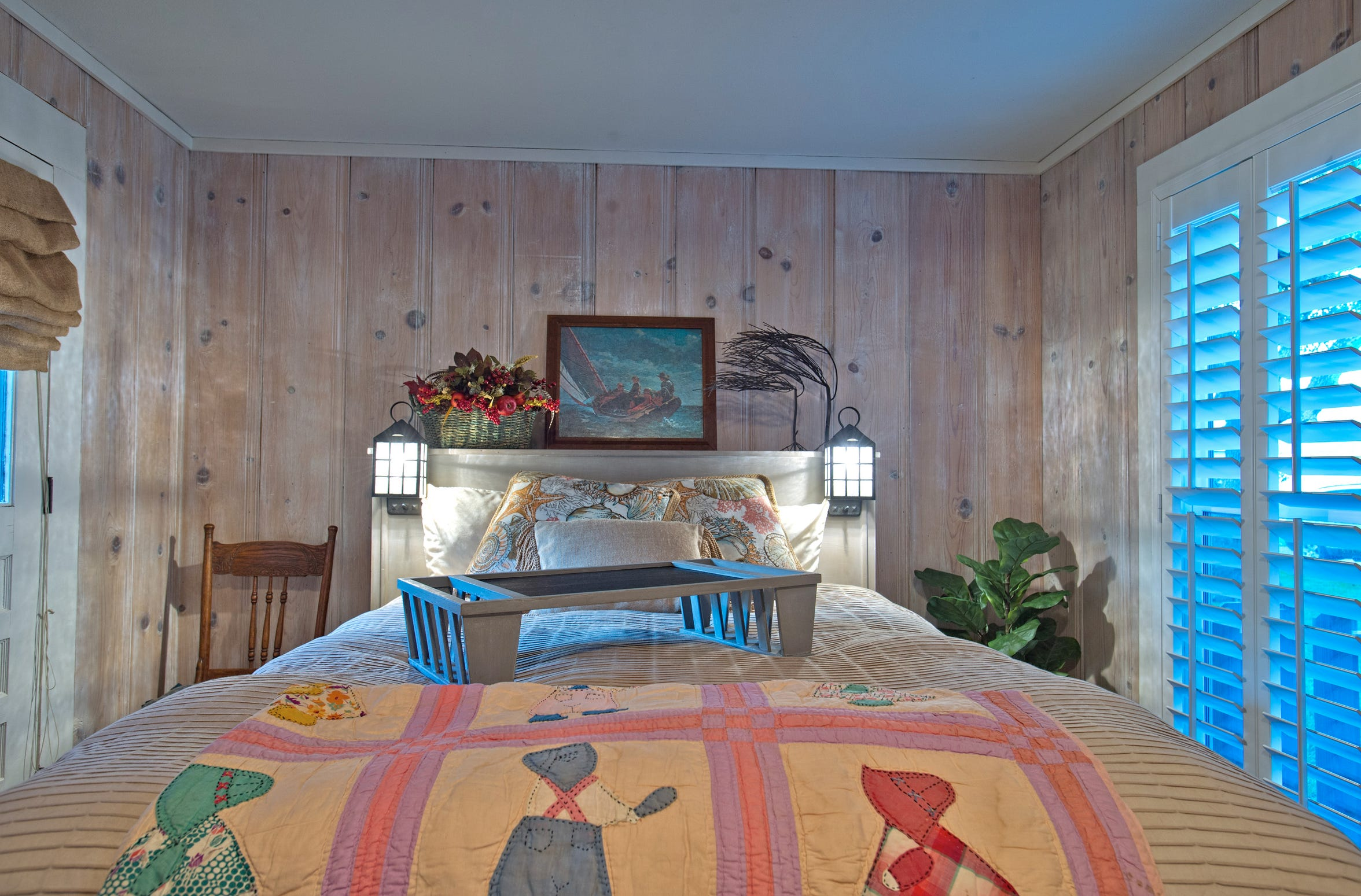 White washed knotty pine paneling surround the bed in the master bedroom creating a peaceful retreat