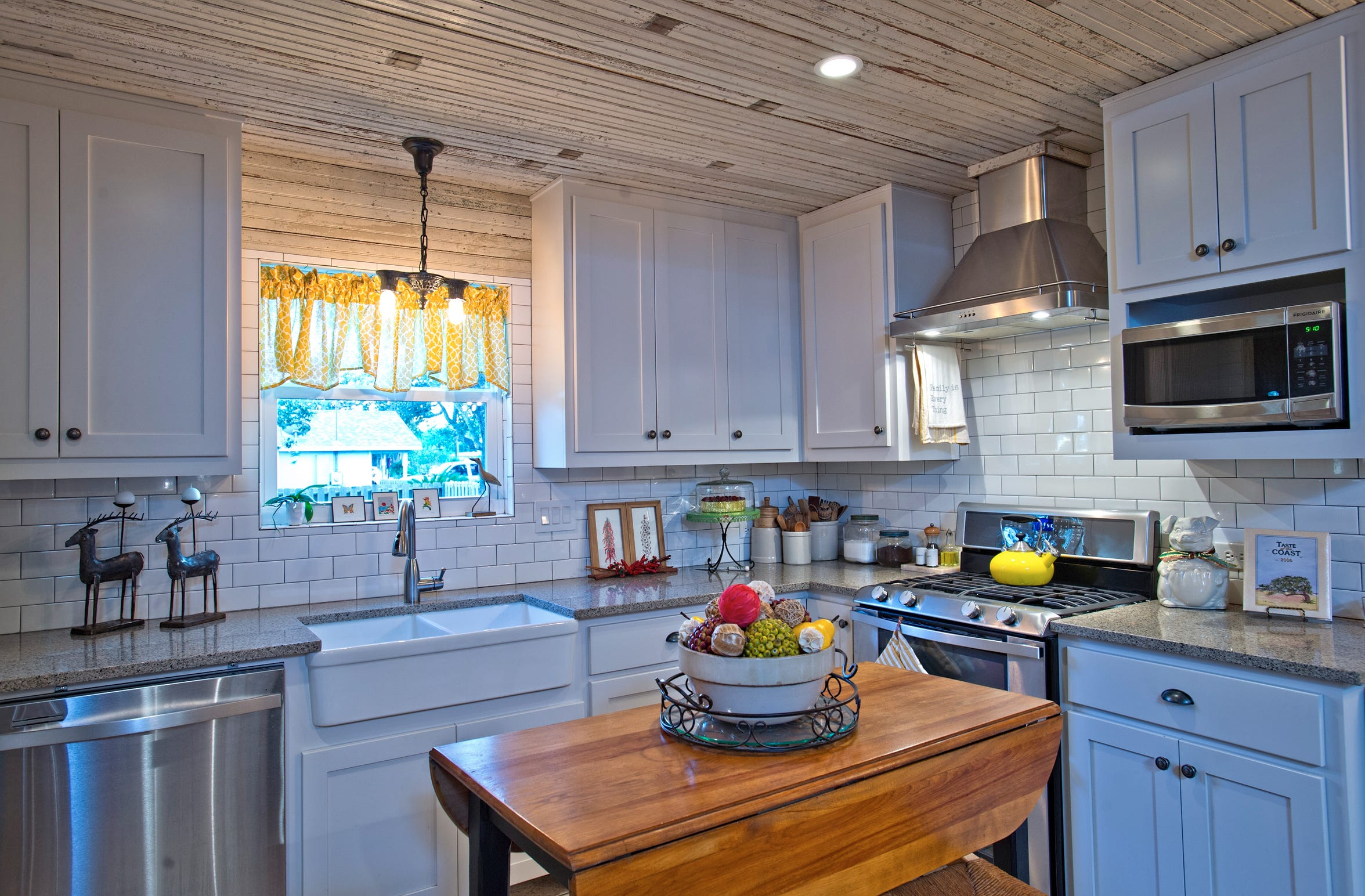 The updated kitchen still has a vintage feel with a white subway tiled backsplash, farm sink and granite counters with a vintage wood plank ceiling