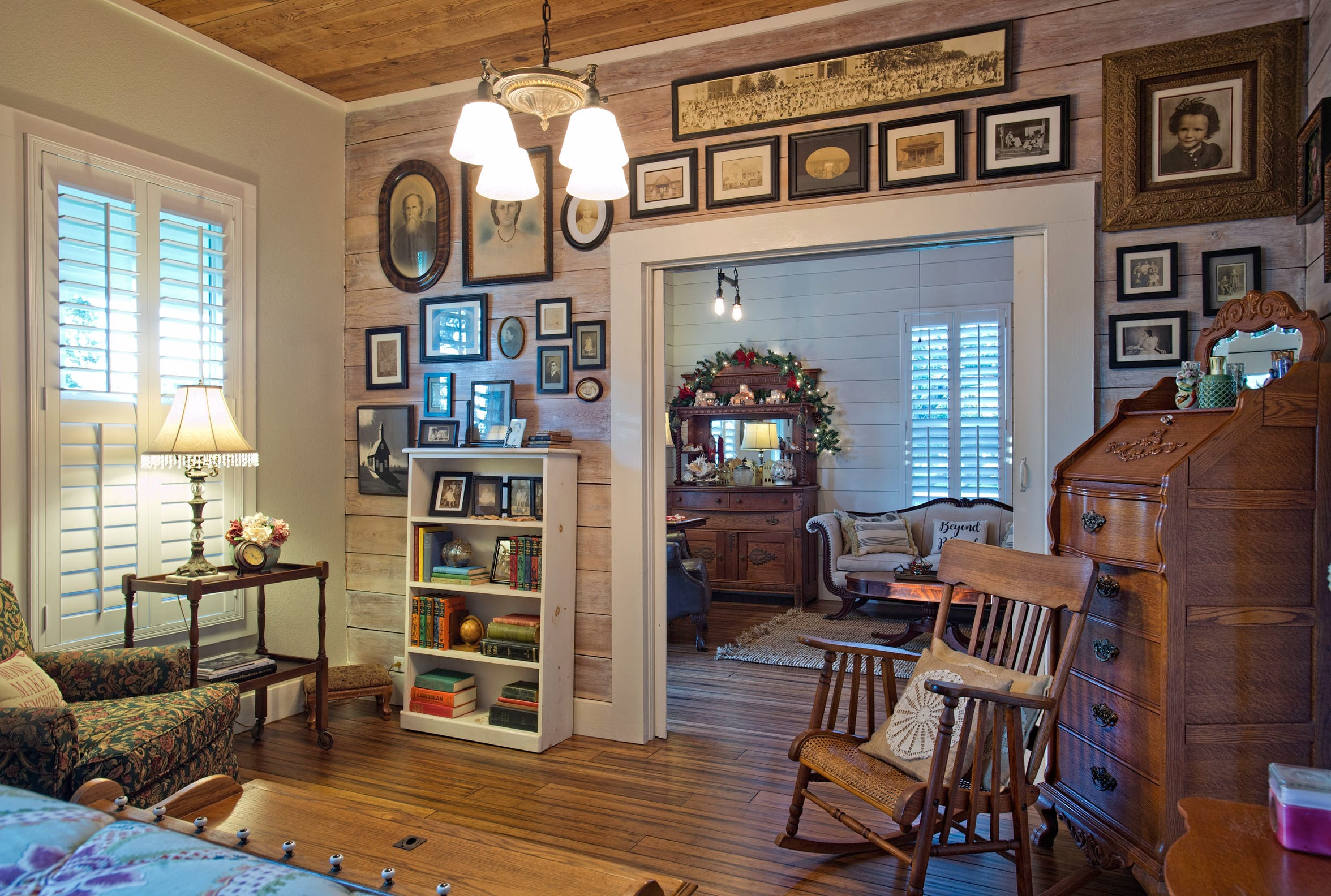 The guest bedroom has a shiplap wood walled sitting area perfect for displaying vintage family photos