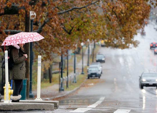 A woman waits to cross Clifton and Dixmyth Ludlow Avenues Thursday, November 15, 2018, as the rain the rain continues to fall. An overnight ice storm caused downed power lines and trees.  According to Duke Energy, 102,267 customers were without power in the region Thursday morning.