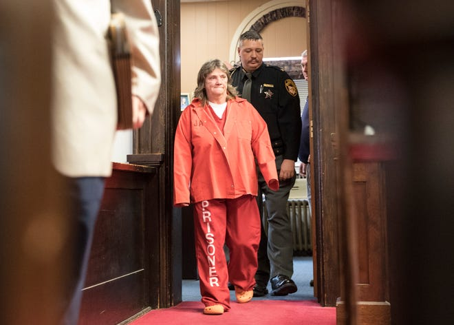 Rita Newcomb, 65, of South Webster is escorted into Judge Randy Deering's Pike County courtroom Thursday afternoon for her arraignment regarding her possible involvement with the murder of the Rhoden family in 2016. Newcomb is accused of perjury and obstructing justice for allegedly misleading investigators; Newcomb also is charged with forging custody documents to cover up the crimes.