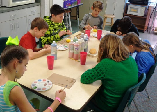 Students from Children's Meeting House Montessori School in Loveland were busy painting snowman ornaments from Whistle Stop Clay Works to benefit their school.