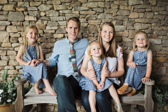 Emily Chapman sits with her husband Tanner and their three daughters