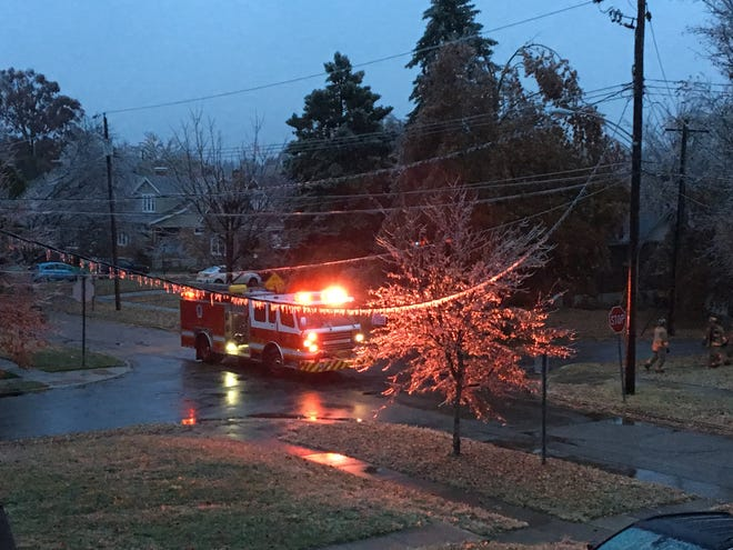 Ice hangs on power lines and trees on Thursday morning on Hildreth Avenue in Westwood as firefighters close off the cross street of Dartmouth Drive with caution tape.