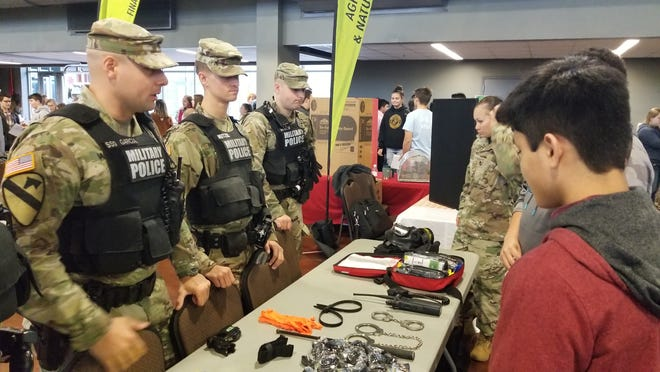 From left to right, Staff Sgt. Edgar Garcia, Pfc. Avery Neitzel, Spc. Brian Hickman, 218th Military Police Company, 716th Military Police Battalion, inform students from the Clarksville-Montgomery County School System about some of the exciting career opportunities afforded by the Army in law enforcement. Students from around the district circulated through static displays by businesses and schools, providing them with the opportunity to explore potential careers after high school. 14 November 2018.