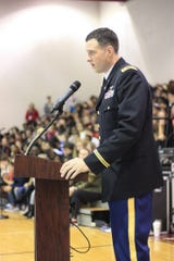 Major Scott Kowalk, 716th Military Police Battalion, addresses a full crowd of students, faculty and veterans at West Creek Middle School for their annual Veterans Day Ceremony on 9 November 2018.