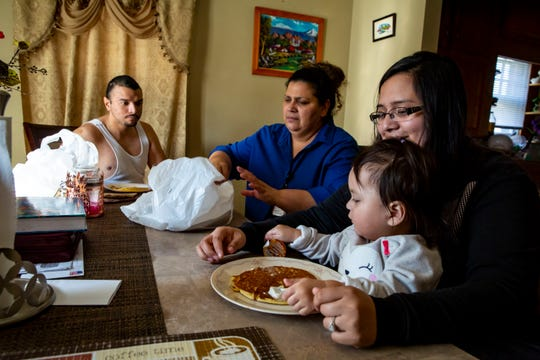 Jairo Morales Landaverde, 25, left, Flor Morales Landaverde, 49,(blue blouse), Gabriela Morales Landaverde(glasses) and Natalie, one and a half, eating lunch at their Des Moines home, Oct. 26, 2018. Over six years ago, Jairo was a victim of a gangattack atthe family's first home, leaving him bloodied on the kitchen floor after he was beat by a crow bar.