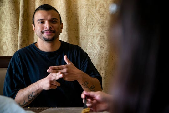 Jairo Morales Landaverde, 25, signs to his sister Gabriela Morales Landaverde during lunch at their Des Moines home, Oct. 26, 2018. Over six years ago, Jairo was a victim of a gangattack atthe family's first home, leaving him bloodied on the kitchen floor after he was beat by a crow bar.