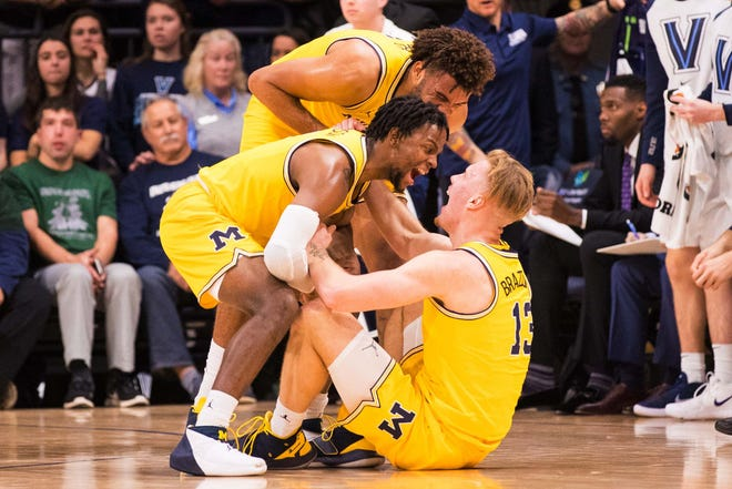 Michigan Wolverines forward Ignas Brazdeikis (13) reacts with forward Isaiah Livers (4) and guard Zavier Simpson (3) after scoring against the Villanova Wildcats during the first half at Finneran Pavilion on Wednesday, Nov. 14, 2018