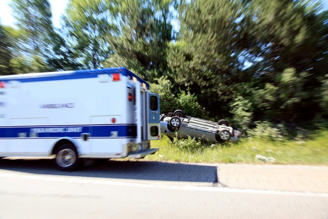 Ambulance speeding by a gray car flipped over