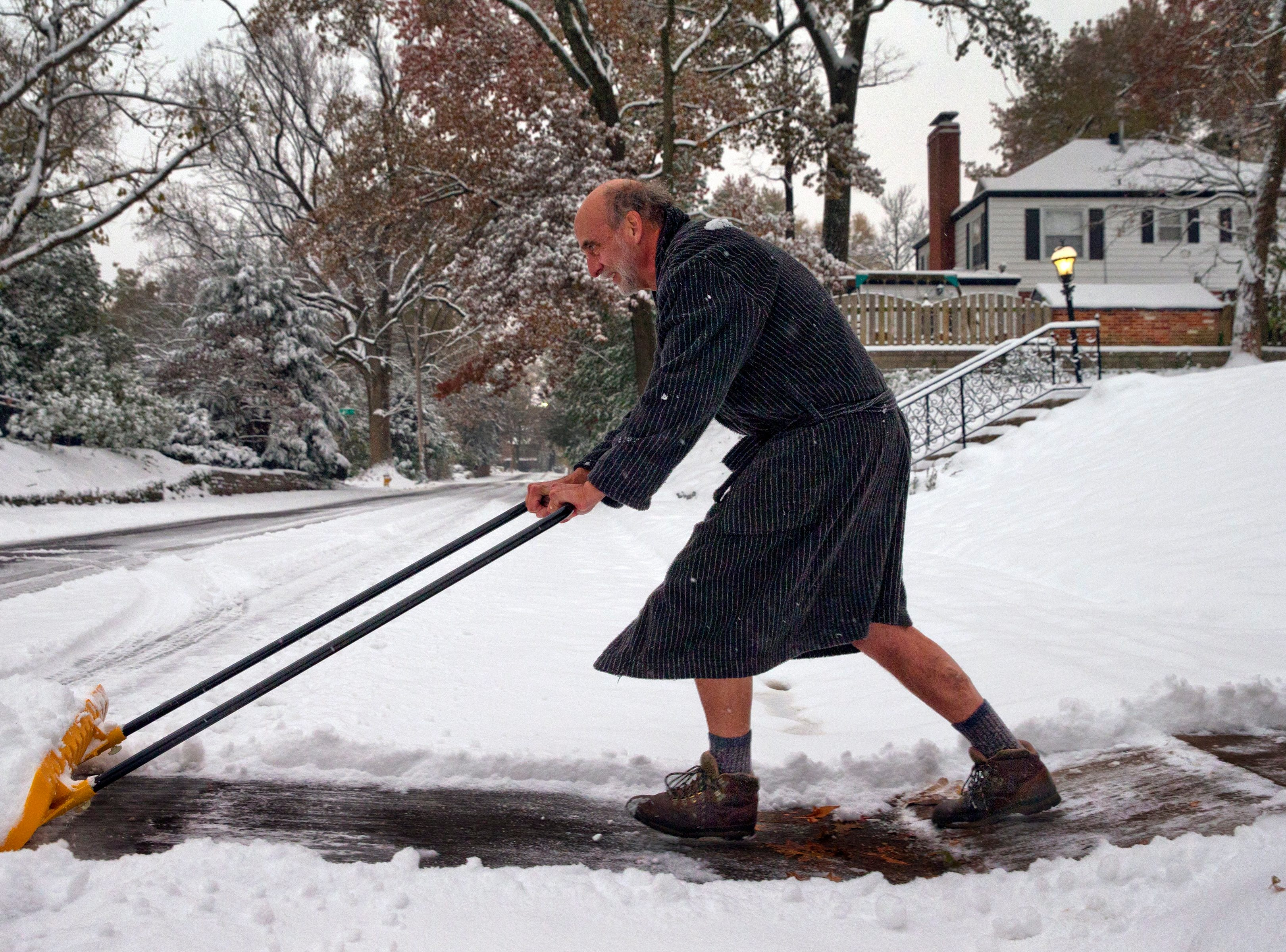 "Richard Burst clears snow from his driveway Thursday, Nov. 15, 2018, in St. Louis.   ""All I really need to accomplish are two lanes for my car,"" he said.   Much of the region had at least 4 inches of snow and forecasters expect about 1 inch or 2 inches more will fall by the time it tapers off around noon Thursday."