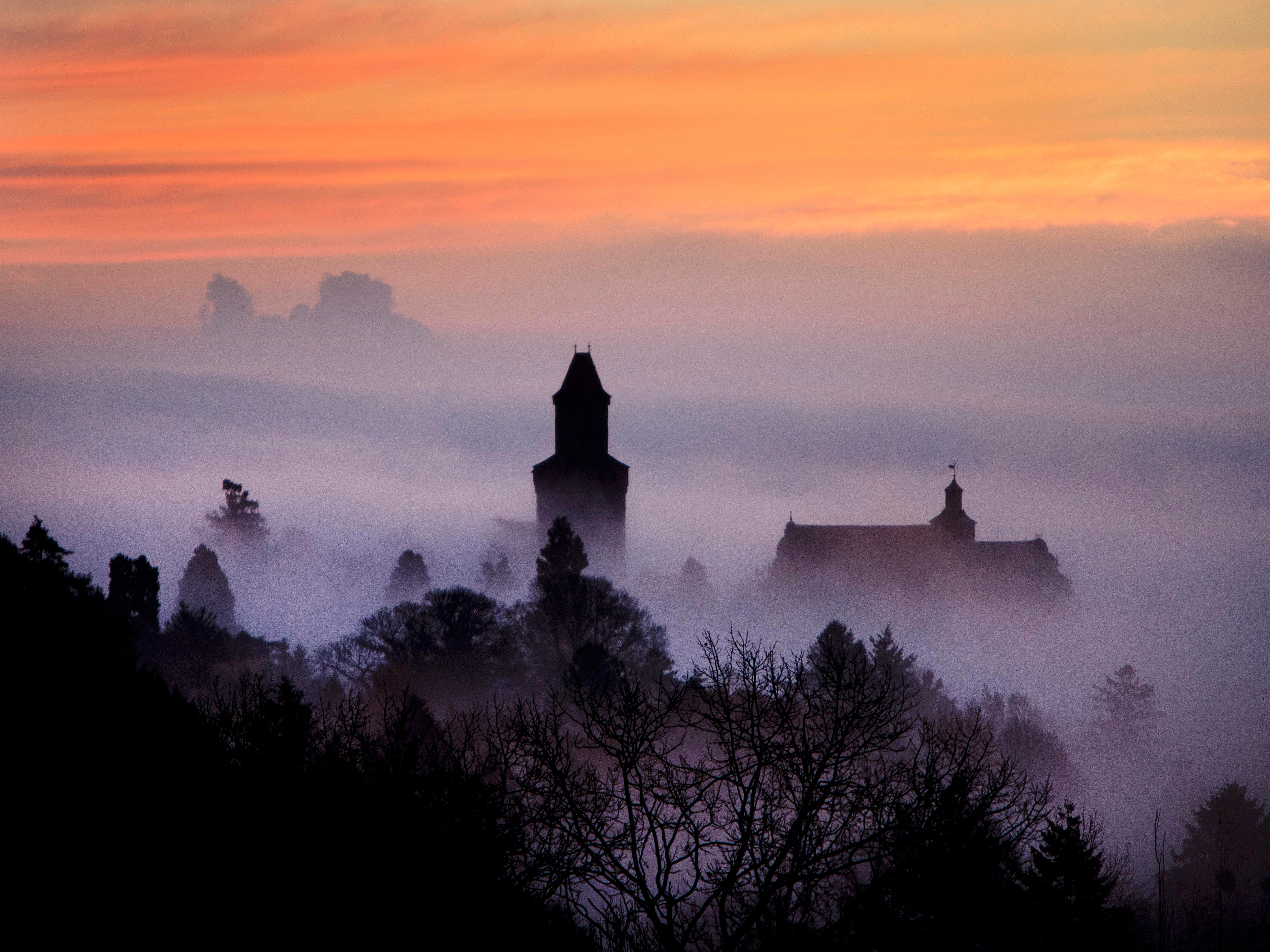 The castle of Kronberg looks out of the fog that covers the city of Frankfurt, Germany, Wednesday, Nov. 14, 2018.