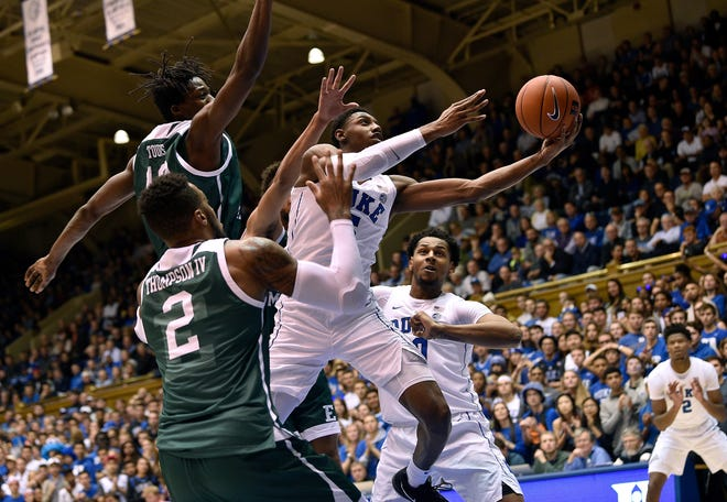 Cam Reddish of the Duke Blue Devils drives between Boubacar Toure and James Thompson IV of the Eastern Michigan Eagles.