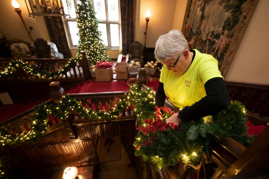 Melody Osgood, of Lansing, decorates the main staircase.
