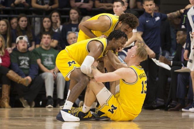 Zavier Simpson and Isaiah Livers of  Michigan celebrate with Ignas Brazdeikis after Brazdeikis made a basket and was fouled in the first half.