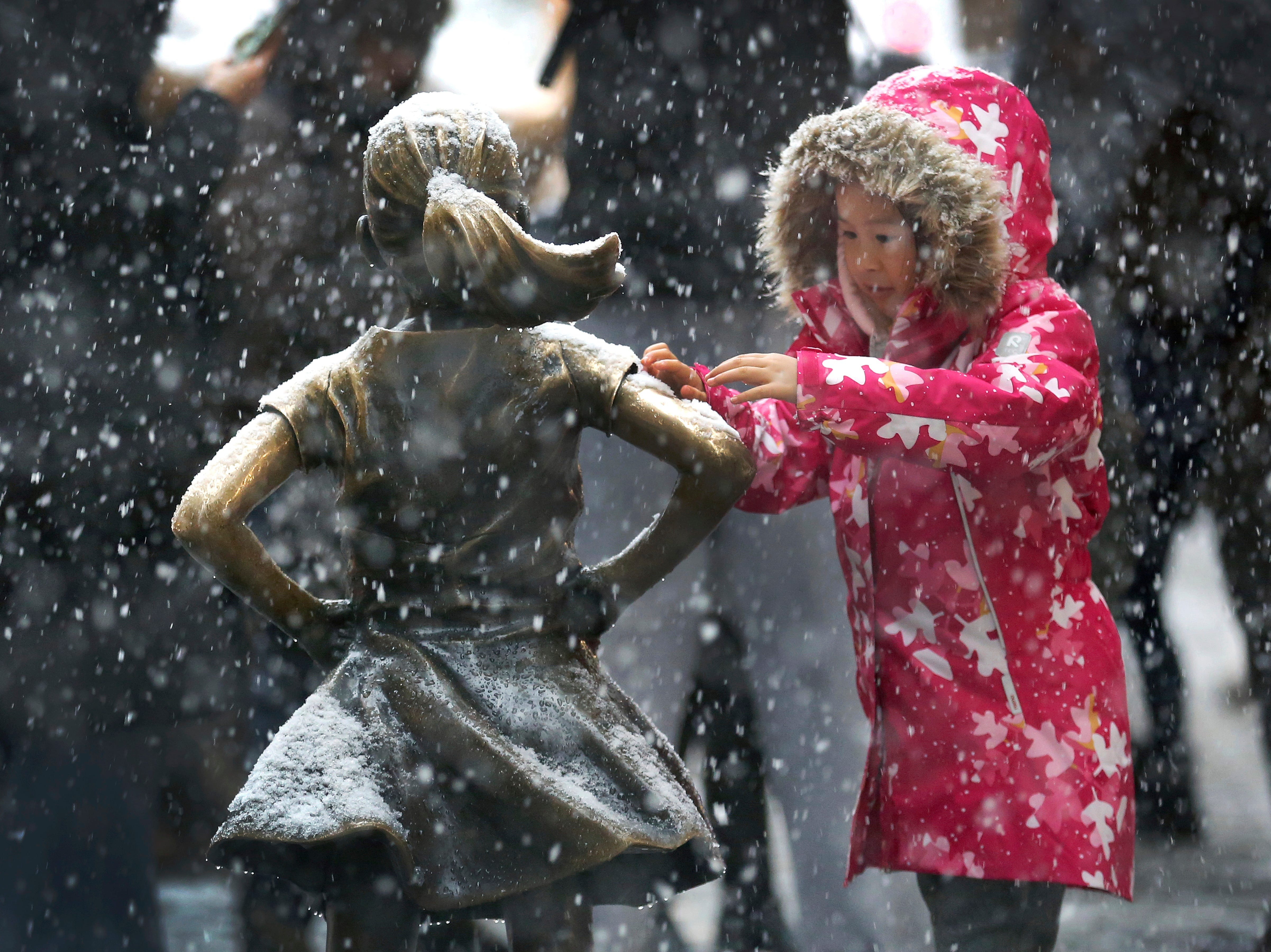 A young girl brushes off snow on the Fearless Girl statue in lower Manhattan on Thursday, Nov. 15, 2018, in New York. One of the first big storms of the season moved across the eastern half of the country on Thursday.