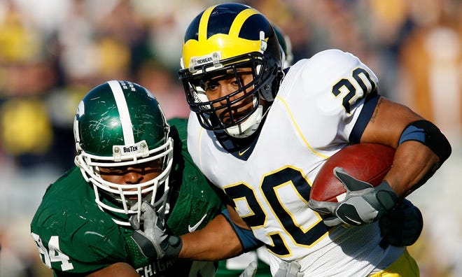 Michigan running back Mike Hart, right, stiff arms the facemask of Michigan State defensive end Jonal Saint-Dic at Spartan Stadium in 2007.