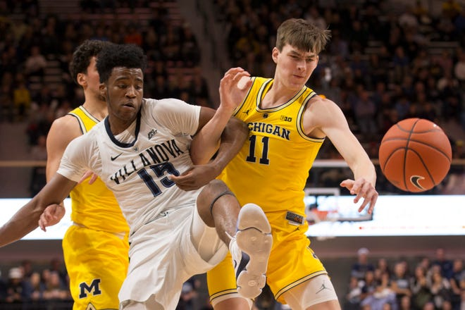 Villanova's Saddiq Bey, left, fights for the control of the basketball with Michigan's Colin Castleton during last season's Gavitt Games matchup.