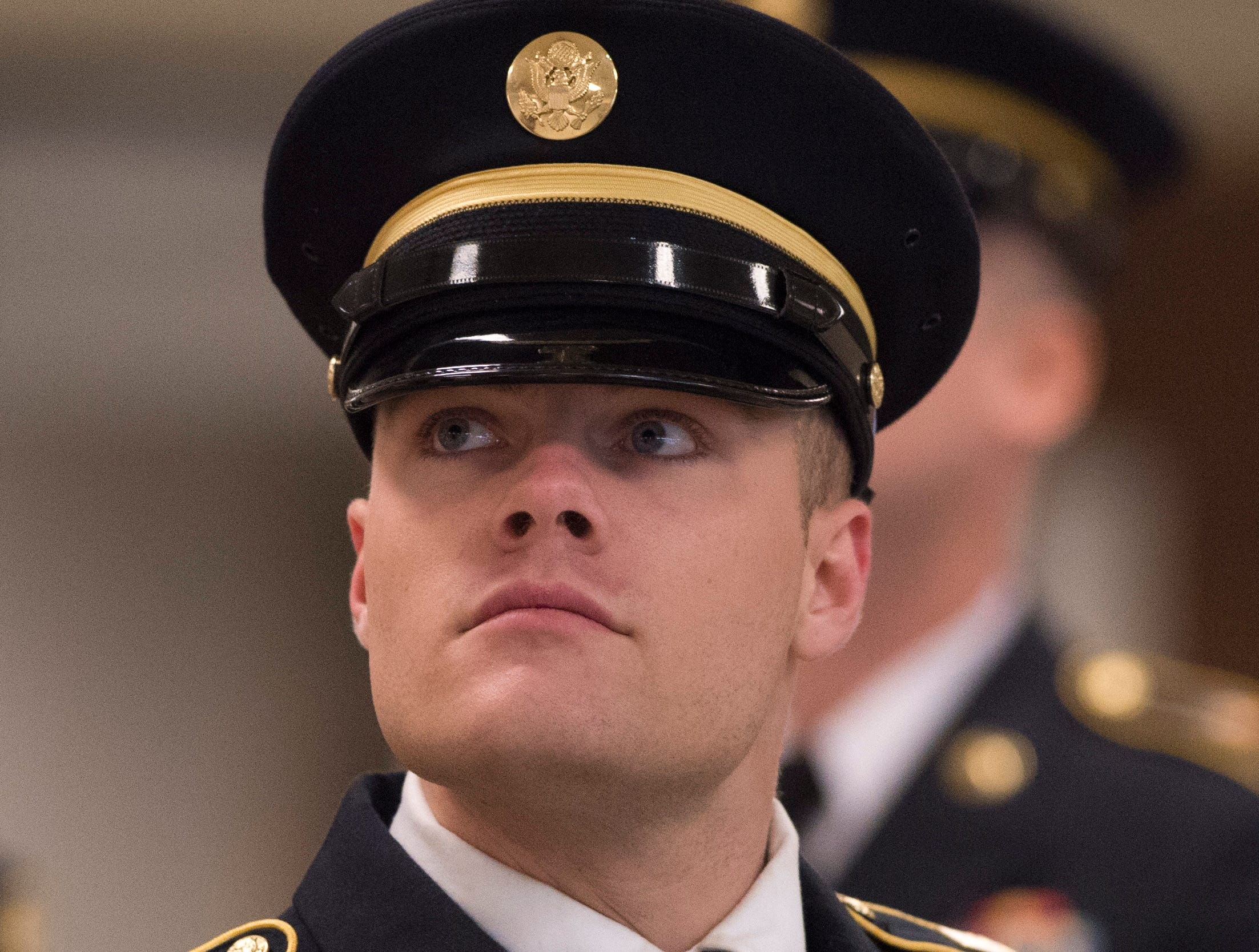 """Private First Class Jagger Wolf looks up at a tv in the lobby of Christian Fellowship Church showing the """"Celebration of Life"""" ceremony for Army Sgt. Drew Watters in Evansville, Ind., Wednesday afternoon, Nov. 14, 2018. The 23-year-old Evansville native was killed in a training accident in his Tacoma, Washington, base."""