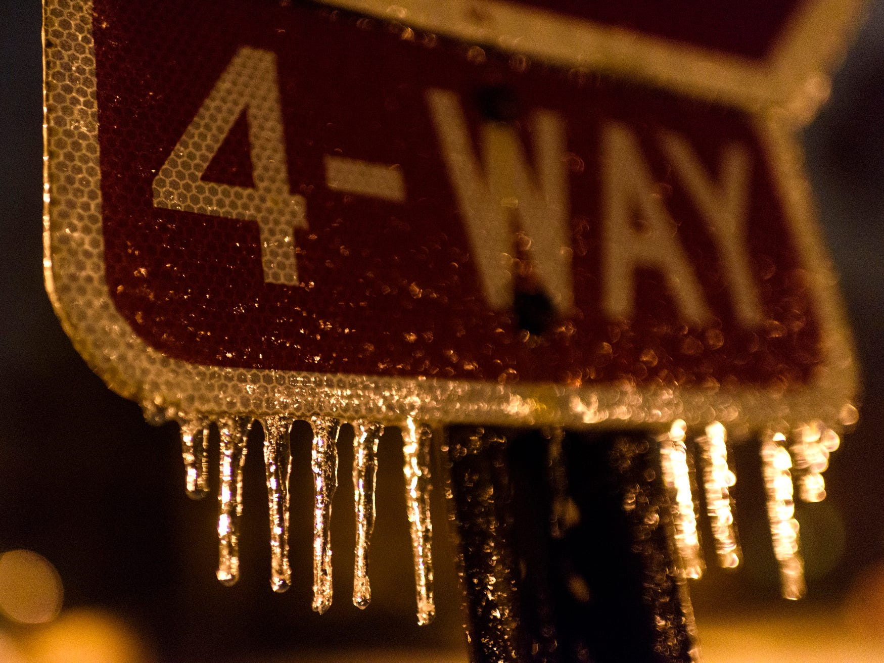 Icicles form on a four-way stop sign at the intersection of First Street and Chandler Avenue in downtown Evansville, Ind., Wednesday, Nov. 14, 2018. A Winter Weather advisory was issued for the Evansville area through 6 p.m. Thursday.