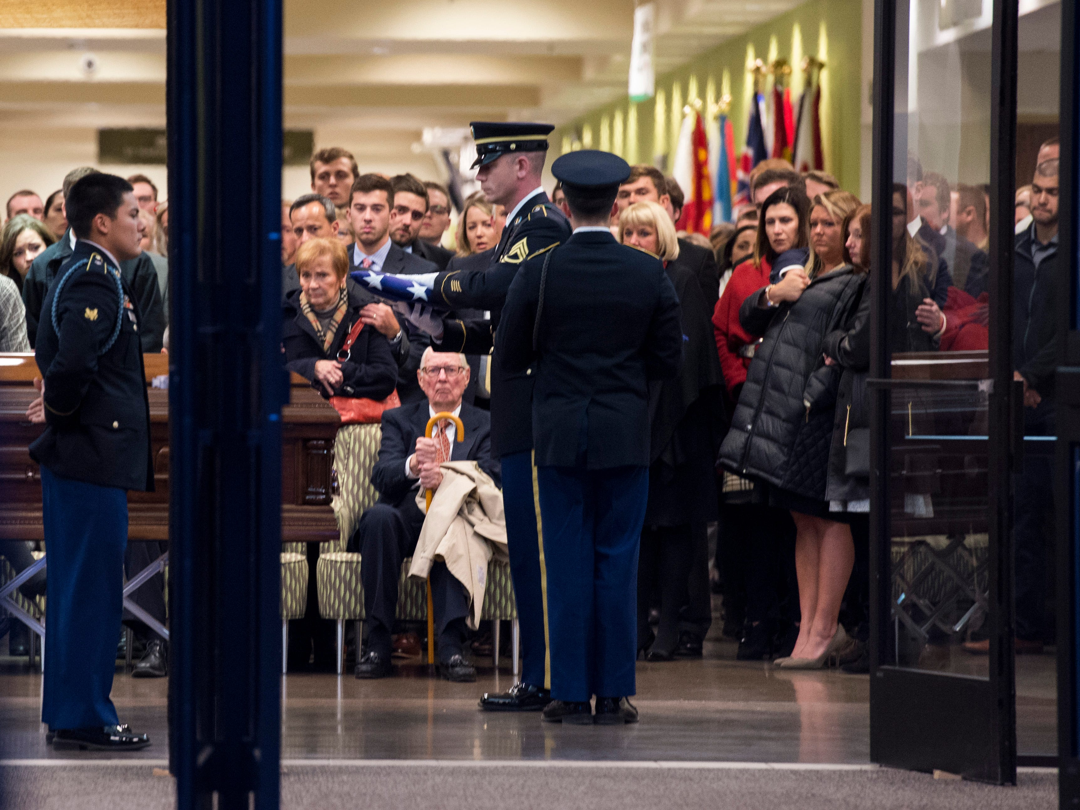 "Sgt. First Class Peno places the flag on the casket before handing it off to a family member in the lobby of Christian Fellowship Church during the ""Celebration of Life"" ceremony for Army Sgt. Drew Watters in Evansville, Ind., Wednesday afternoon, Nov. 14, 2018. The 23-year-old Evansville native was killed in a training accident in his Tacoma, Washington, base."