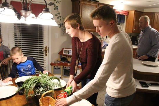 Lexi Evarts and boyfriend Jay Conner set the table dinner at Lexi's parent's house in Gibsonburg.