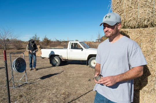 Taylor Reed leans against a stack of hay bales as fellow resident Dakota Mason works to build a fence for the cows at Harvest Farm in Wellington on Wednesday, November 14, 2018. Reed, from Wiley in southeast Colorado, struggled with addiction for his entire life until this spring when he began living at the rehabilitation facility.
