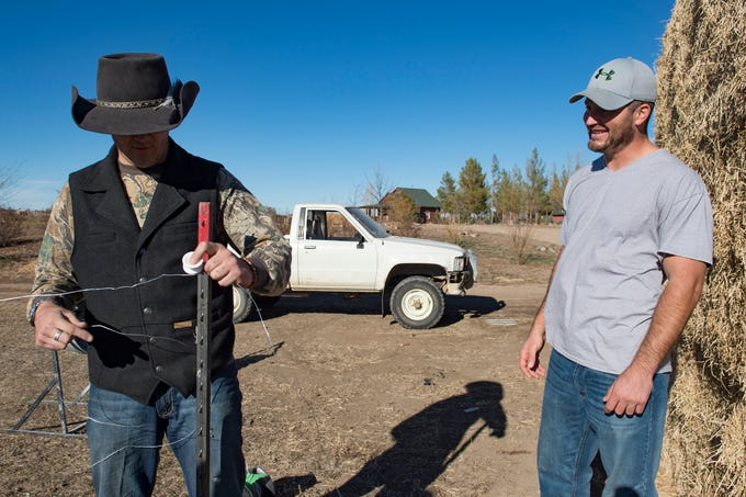 Taylor Reed visits with fellow resident Dakota Mason as he works to build a fence for the cows at Harvest Farm in Wellington on Wednesday, November 14, 2018. Reed, from Wiley in southeast Colorado, struggled with addiction for his entire life until this spring when he began living at the rehabilitation facility.