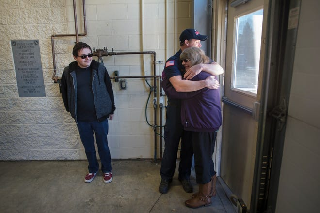 Firefighter Brian Parker hugs Karen Johnson while Johnson's son Jason looks on during a visit to the station on Tuesday, Nov. 13, 2018, at Poudre Fire Authority Station 5 in Fort Collins, Colo. Johnson, a cashier at King Soopers and friend of the firefighters at the station, was recently given Parker's car, paid for and fixed up by the firefighters at Station 5, after hearing that Johnson was undergoing treatment for cancer and had no vehicle to help her get around.