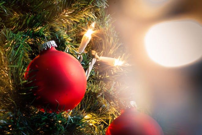 A christmas ball on a christmas treen behind christmas lights