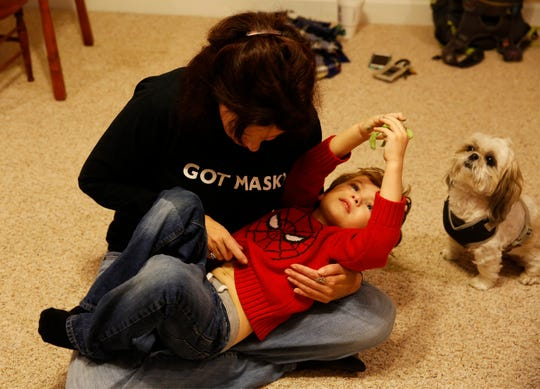 Kimilee Bryant tickles her son Aidan Bryant, 4, in their home in Greenville County Thursday, Nov. 15, 2018 next to their dog, Gypsy.