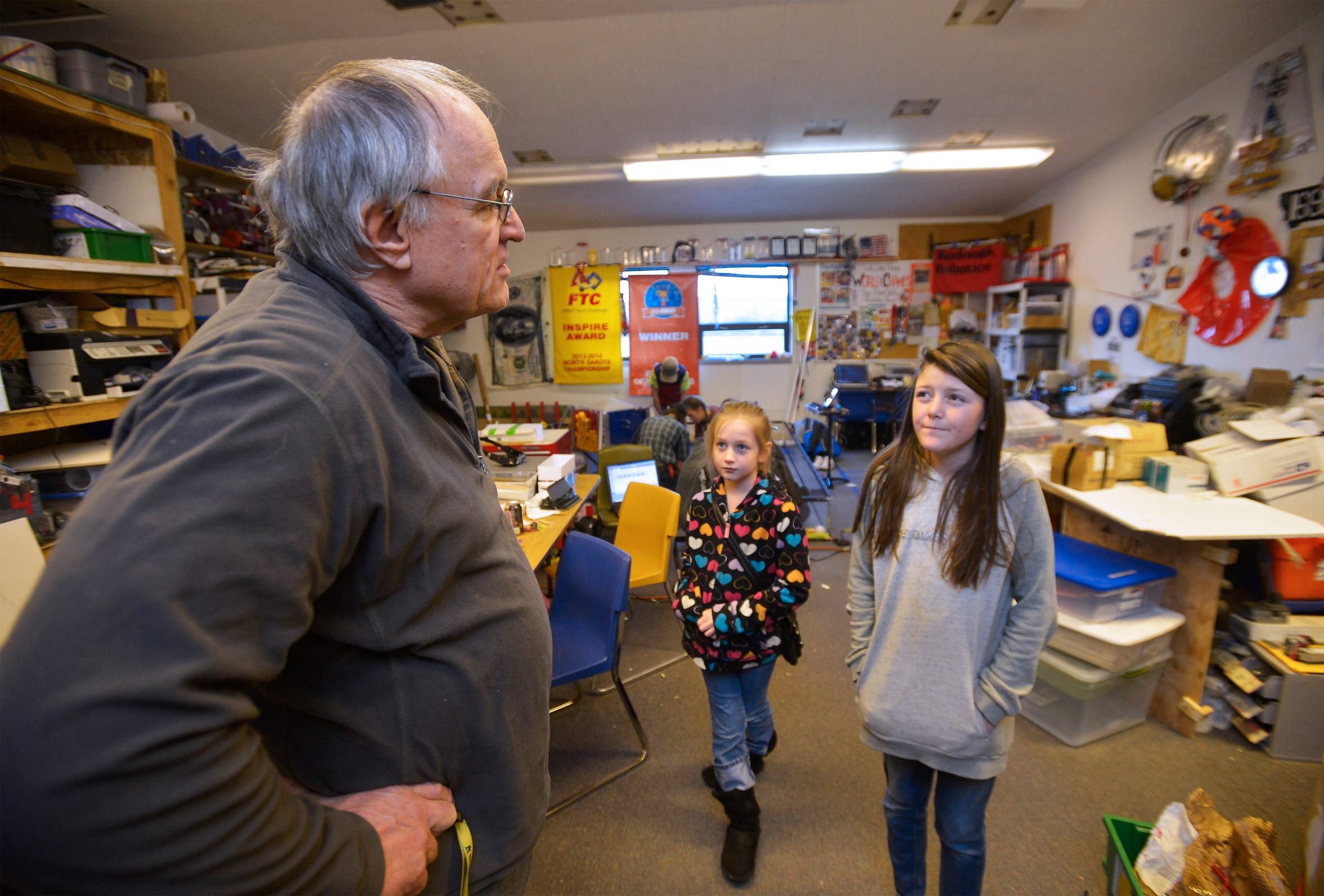 Chuck Merja discusses a robot project with Kenna Brooks, age 9, and Christine Webster, age 12, during Sun River robotics team meeting recently. Merja, who was in a life-threatening farm accident in May of this year, has recovered enough to return to his coaching and mentoring role with the team.