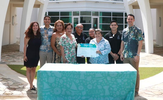 Guam Museum Director Dominica Tolentino, joined by Guam Museum staff and Guam Visitors Bureau representatives, takes the Håfa Pledge on Nov. 4 to celebrate the museum's second anniversary. From left: Perpetua San Agustin, Guam Museum; Josh Tyquiengco, GVB public information officer; Jodiann Santos, Guam Museum; Pauline Okada, Guam Museum; Mark Lord, Guam Museum; Raelene Pascual, Guam Museum; Tolentino; Alex Gagarin, Guam Museum and Nate Denight, president and CEO of GVB.
