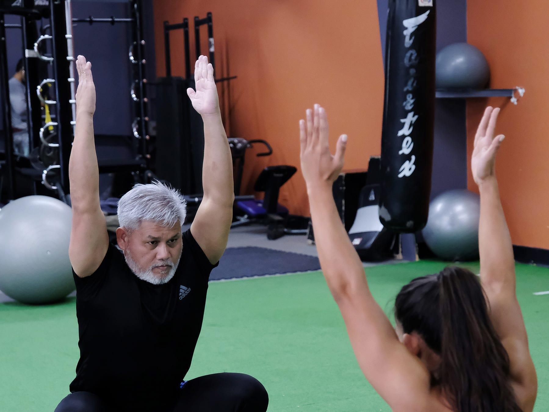 Steve Oshiro does a warm up exercise with Jeralyn Mesa at Paradise Fitness in Hagatna November 15, 2018.