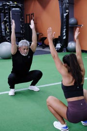 Steve Oshiro does a warm up exercise with Jeralyn Mesa at Paradise Fitness in Hagåtña Nov. 15, 2018.