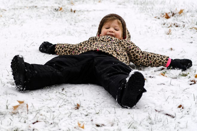 Emmy Phelps, 4, attempts to make a snow angel in downtown Henderson, Ky., Thursday morning, Nov. 15, 2018. The task proved to be a little tricky due to a layer of ice mixed in with the snowfall.