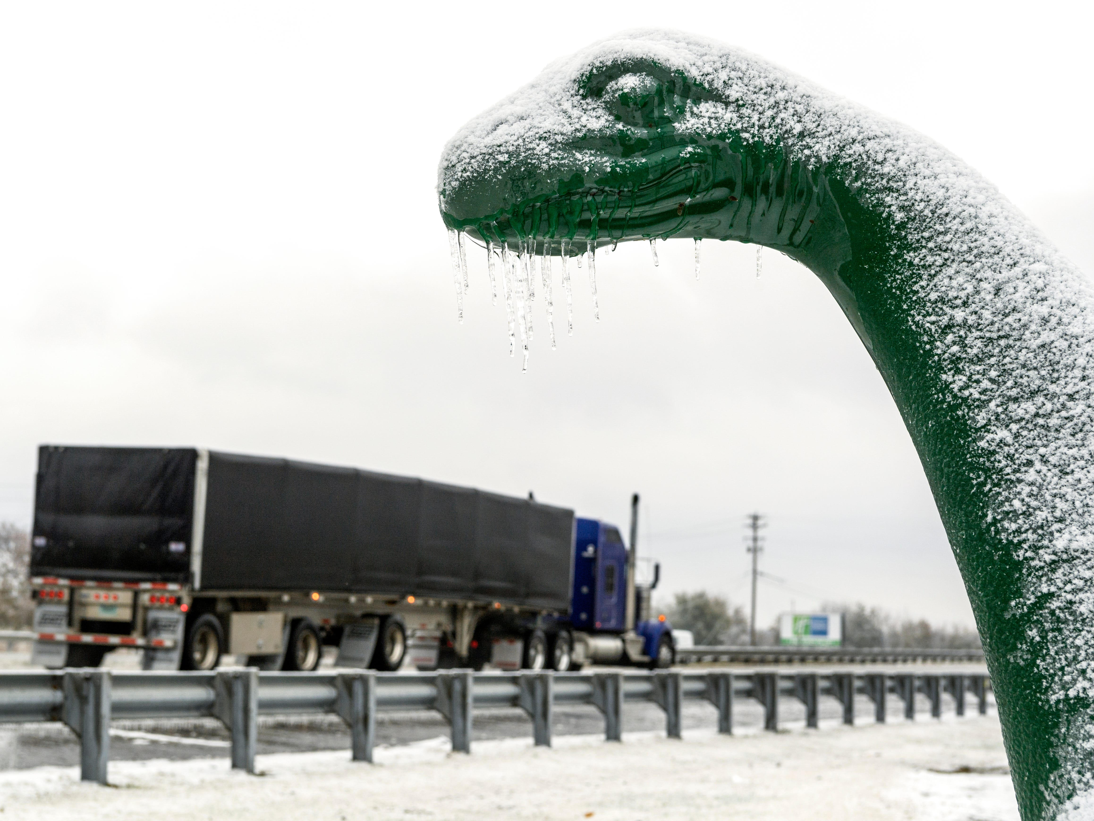 Icicles hang off the dinosaur outside of the Sinclair gas station near the Twin Bridges on US-41 in Henderson, Ky., Thursday, Nov. 15, 2018.