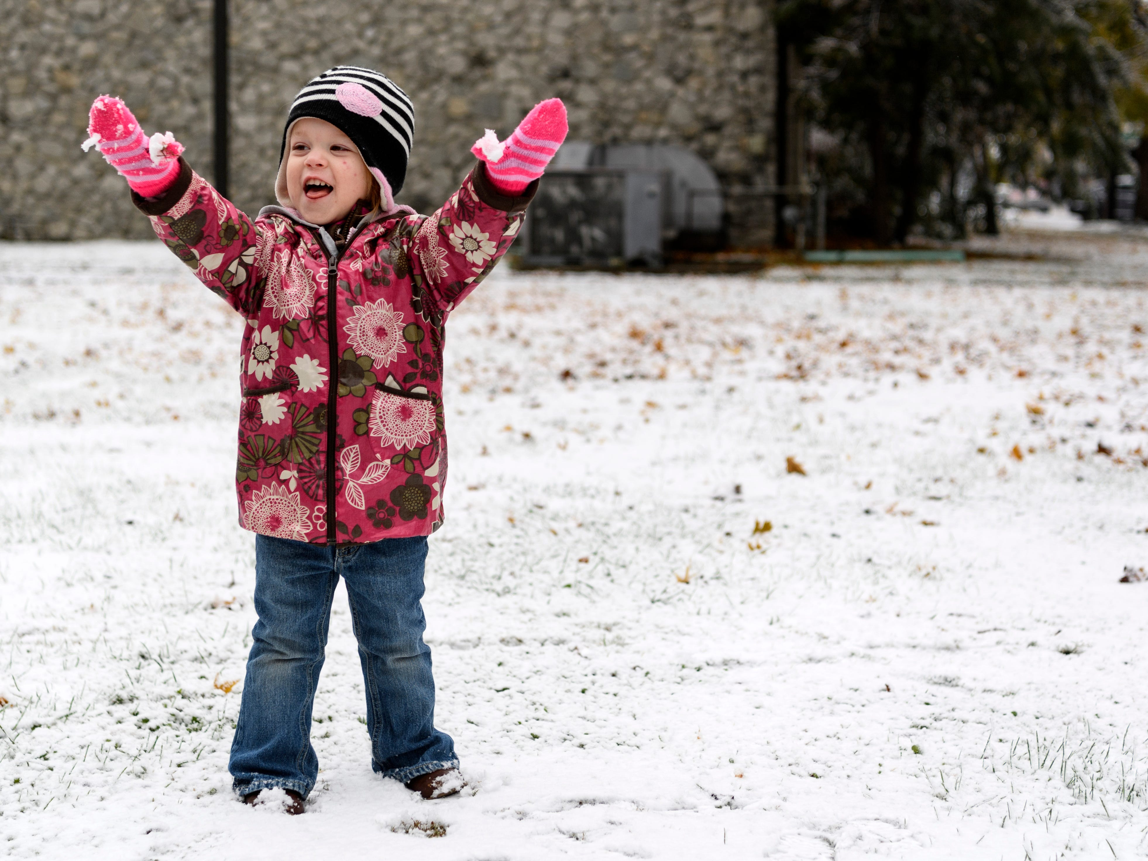 """London Phelps, 2, shows off the icy snow ball stuck to her gloves during a walk to the Henderson County Public Library with her sisters, Emmy, 4, and Harper, 2-months-old, and mother, Whitney Phelps, in downtown Henderson, Ky., Thursday, Nov. 15, 2018. """"We thought we would go to the library to see if we could check out the movie 'Frozen' and watch it at home with some popcorn during our snow day,"""" Whitney said."""
