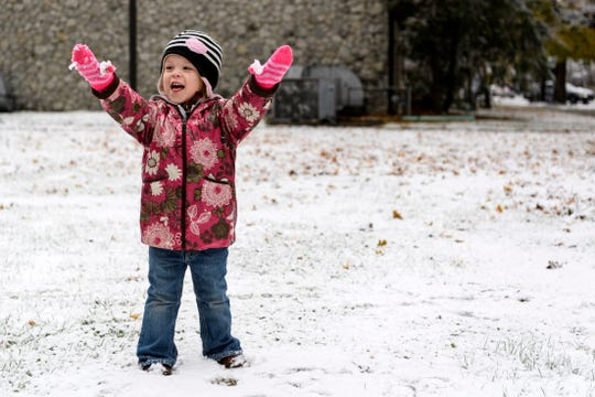 "London Phelps, 2, shows off the icy snow ball stuck to her gloves during a walk to the Henderson County Public Library with her sisters, Emmy, 4, and Harper, 2-months-old, and mother, Whitney Phelps, in downtown Henderson, Ky., Thursday, Nov. 15, 2018. ""We thought we would go to the library to see if we could check out the movie 'Frozen' and watch it at home with some popcorn during our snow day,"" Whitney said."