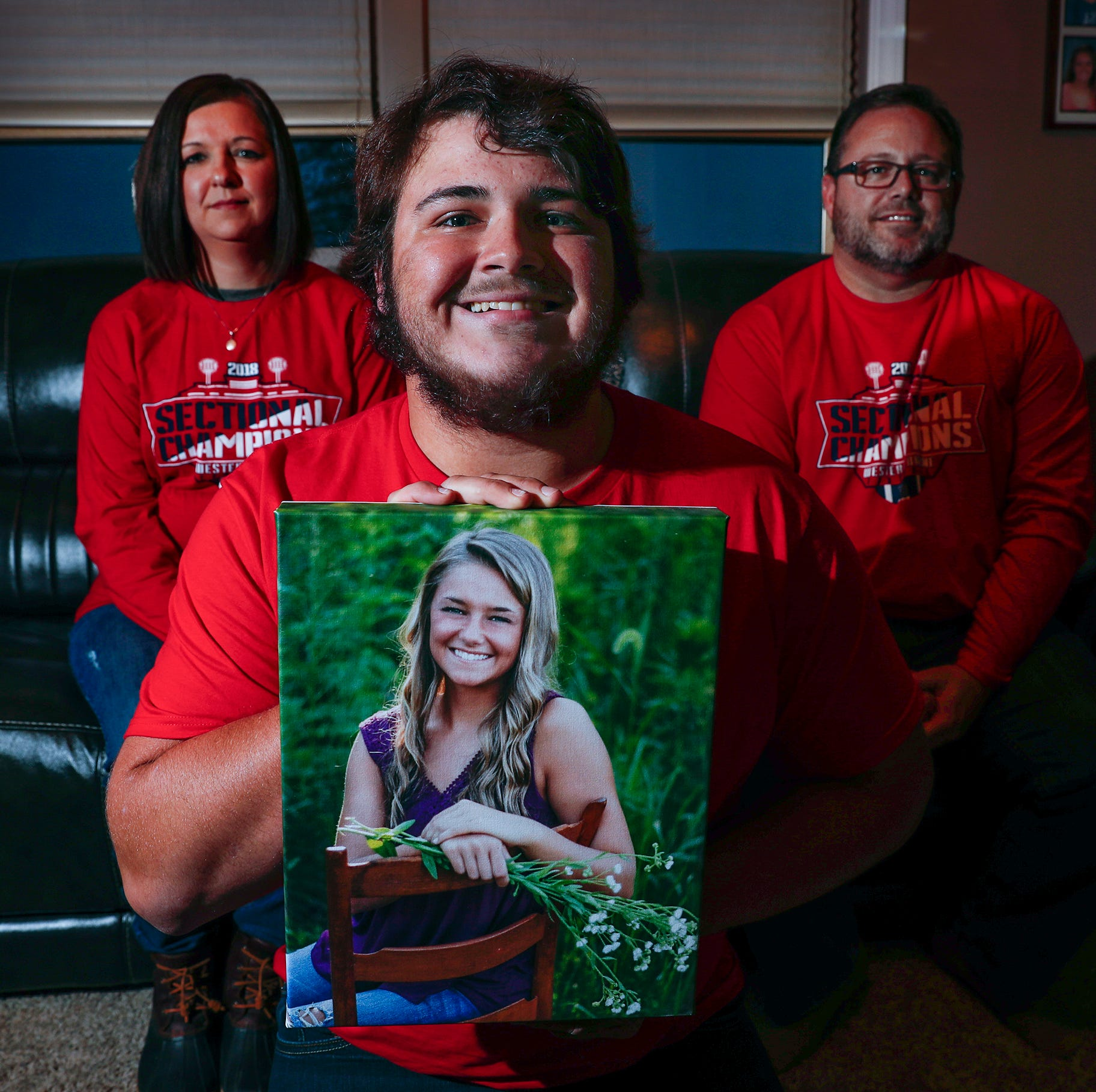 Casey Foster, a Western Boone football player, holds a photo of his sister Sydney, who died in a car accident in March, as his parents Phil and Kristi look on in their home in Jamestown, IN. on Wednesday, Nov. 14, 2018.