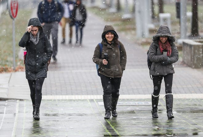 Pedestrians bundle up to travel across the IUPUI campus in Indianapolis, Thursday, Nov. 15, 2018. An overnight wintry mix left Indianapolis covered in freezing rain and snow Thursday morning and afternoon.