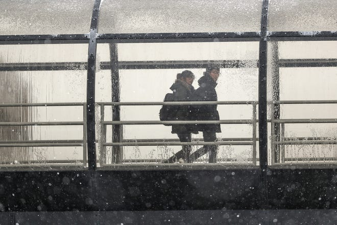 Pedestrians look out at falling snow and stay warm inside a pedestrian walkway on IUPUI's campus in Indianapolis, Thursday, Nov. 15, 2018. An overnight wintry mix left Indianapolis covered in freezing rain and snow Thursday morning and afternoon.