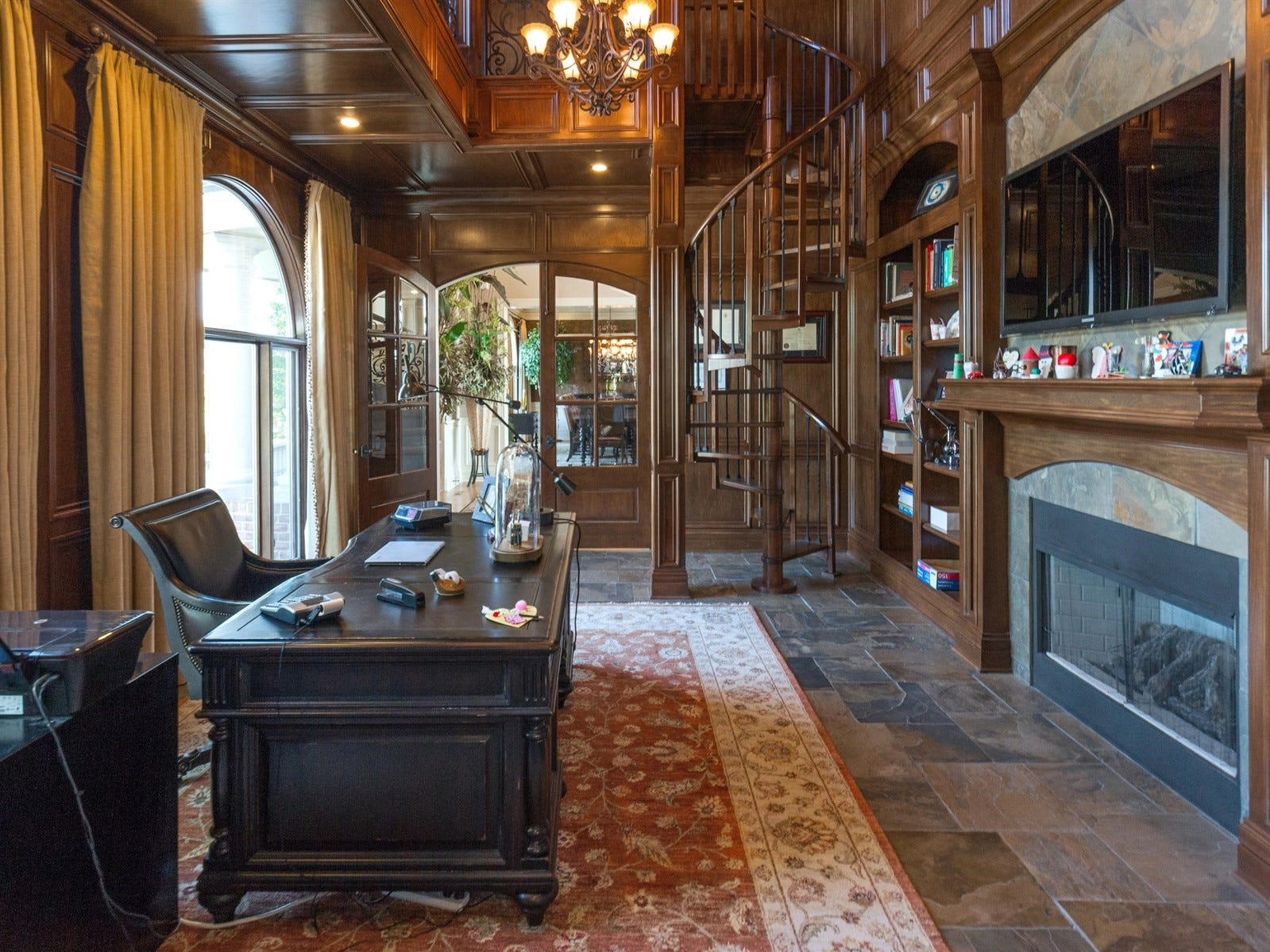 Office and two story library features a spiral staircase and fireplace